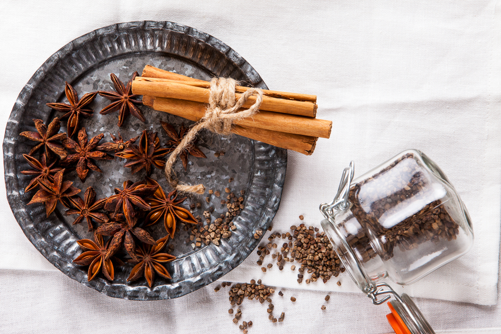 "Decorative, sparse christmas arrangement with greeting card copyspace for ""Merry Christmas""-text. Cinnamon sticks, star anise and cardamom on white table cloth."