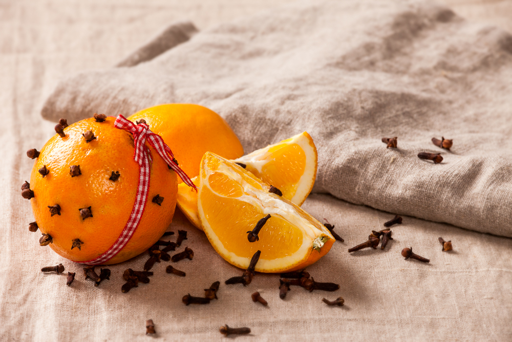 """Decorative, sparse christmas arrangement with greeting card copyspace for """"Merry Christmas""""-text. Orange with clover and ribbon on a brown table cloth. Shallow focus."""